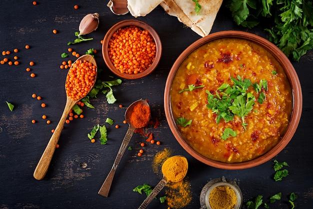 Lentilhas indianas tradicionais da sopa. caril picante indiano dhal na tigela, especiarias, ervas, mesa de madeira preta rústica