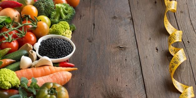 Lentilhas pretas cozidas em uma tigela com legumes em uma mesa de madeira