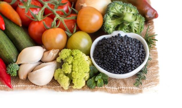 Lentilhas pretas cruas em uma tigela com vegetais isolados no branco