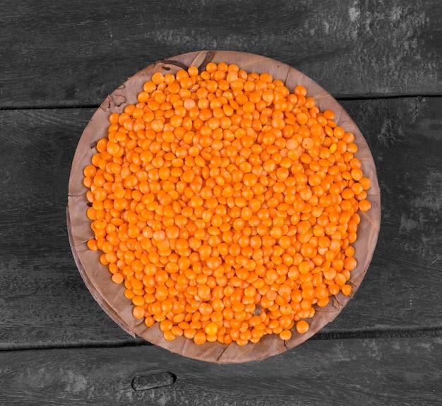 Lentilhas vermelhas ou masoor dal em fundo de madeira