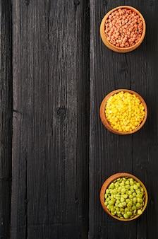 Lentilhas vermelhas, verdes e amarelas em um fundo preto de madeira Foto Premium