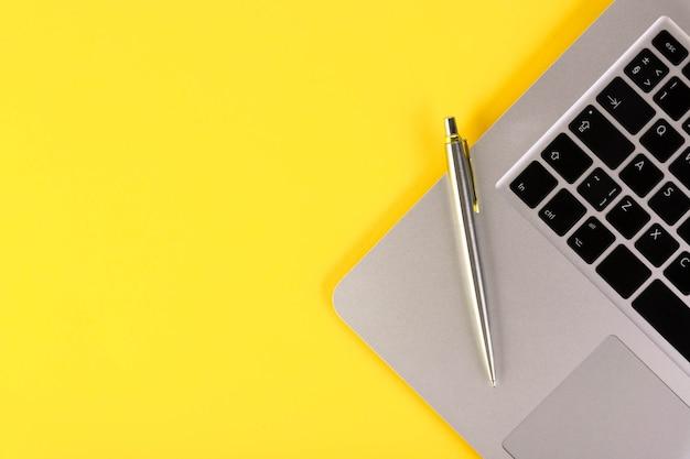 Leptop, caderno, caneta, em um amarelo