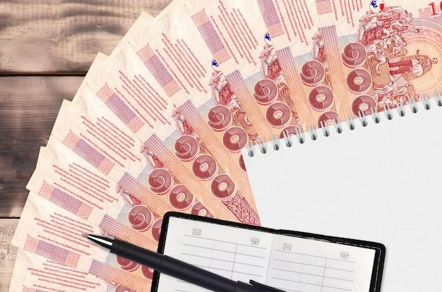 Leque com 100 notas de baht tailandês e bloco de notas com livro de contatos e caneta preta