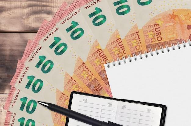 Leque de notas de 10 euros e bloco de notas com livro de contactos e caneta preta. conceito de planejamento financeiro e estratégia de negócios. contabilidade e investimento