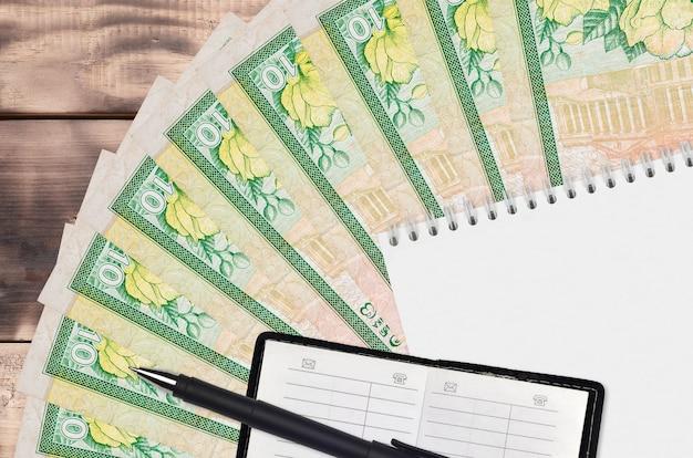 Leque de notas de 10 rúpias do sri lanka e bloco de notas com livro de contato