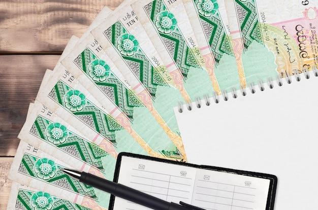 Leque de notas de 10 rúpias do sri lanka e bloco de notas com livro de contatos e caneta preta