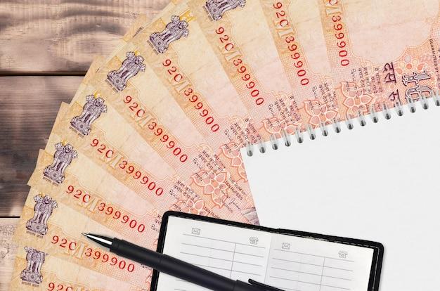 Leque de notas de 10 rúpias indianas e bloco de notas com livro de contatos e caneta preta