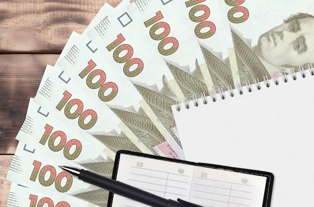 Leque de notas de 100 hryvnias ucranianas e bloco de notas com livro de contatos e caneta preta