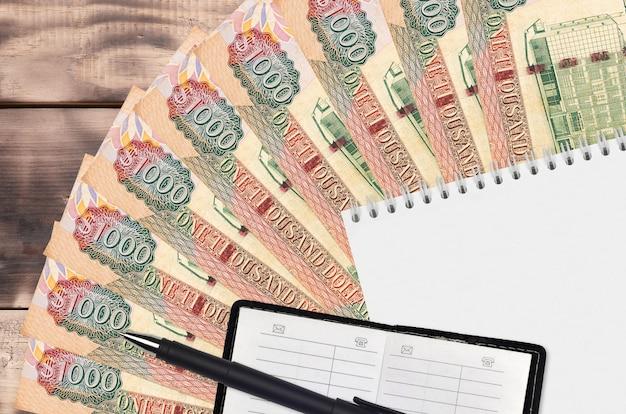 Leque de notas de 1000 dólares guianenses e bloco de notas com livro de contactos e caneta preta