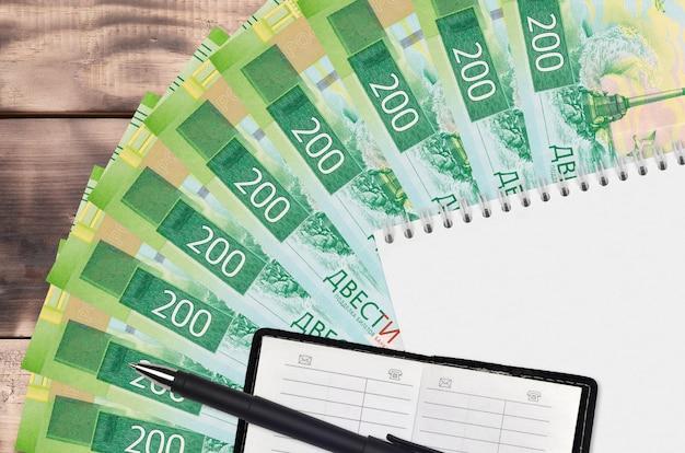 Leque de notas de 200 rublos russos e bloco de notas com livro de contatos e caneta preta