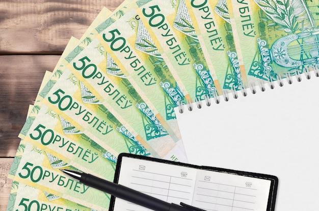 Leque de notas de 50 rublos bielorrussos e bloco de notas com livro de contatos e caneta preta