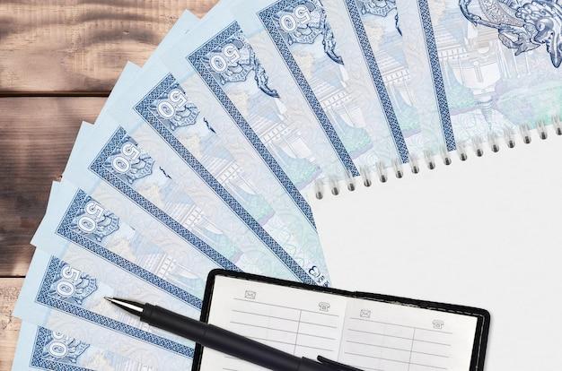 Leque de notas de 50 rupias do sri lanka e bloco de notas com livro de contatos e caneta preta