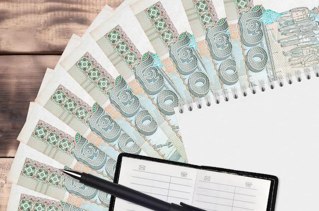 Leque de notas de baht tailandês e bloco de notas com livro de contatos e caneta preta