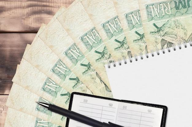 Leque de notas de reais e bloco de notas com livro de contatos e caneta preta