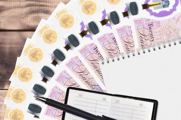 Leque de notas em libras esterlinas e bloco de notas com livro de contatos e caneta preta