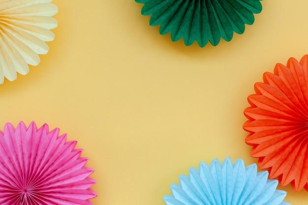 Leques de papel colorido de aniversário festivo em amarelo pastel ou festa