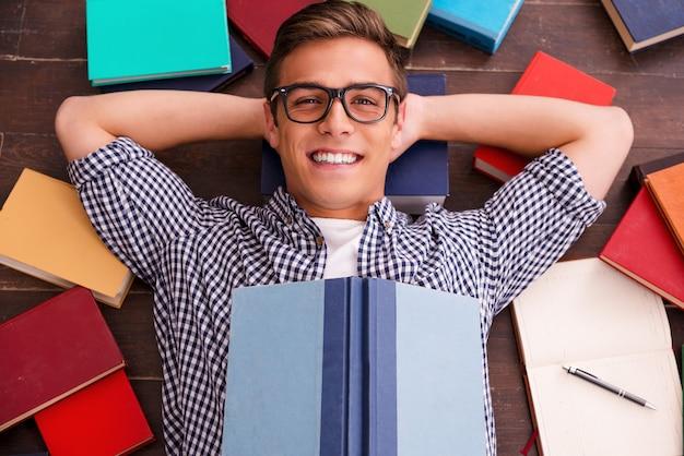 Ler é meu hobby! vista superior de um jovem feliz, segurando as mãos atrás da cabeça e sorrindo enquanto está deitado no chão de madeira com livros coloridos ao redor