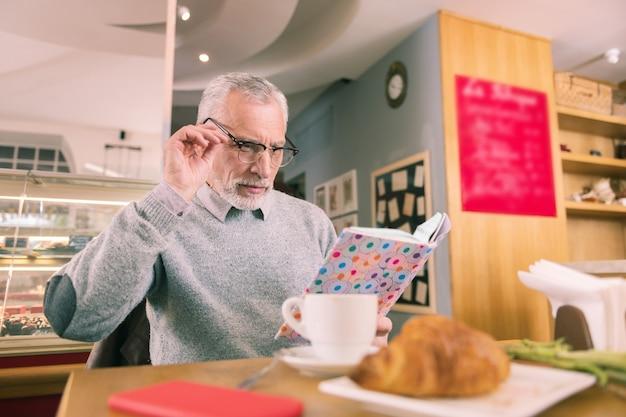Ler livro. homem barbudo de óculos lendo livro enquanto passa a manhã em uma padaria francesa