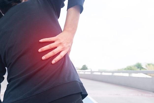 Lesão de dor nas costas da mulher durante o treinamento com a mão segurando.