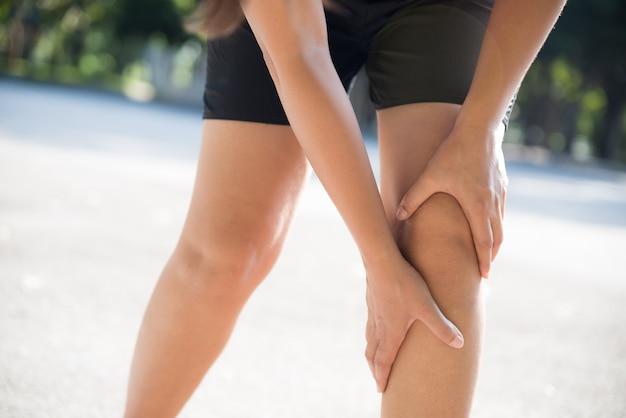 Lesão de joelho esporte corredor. dor do joelho da mulher ao correr no jardim.