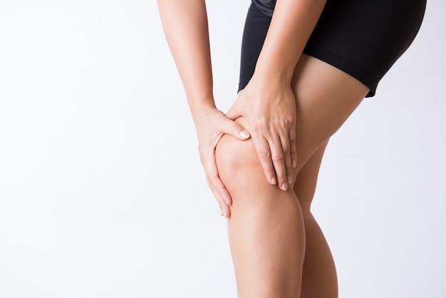 Lesão de joelho esporte corredor. jovem mulher do close up na dor do joelho.