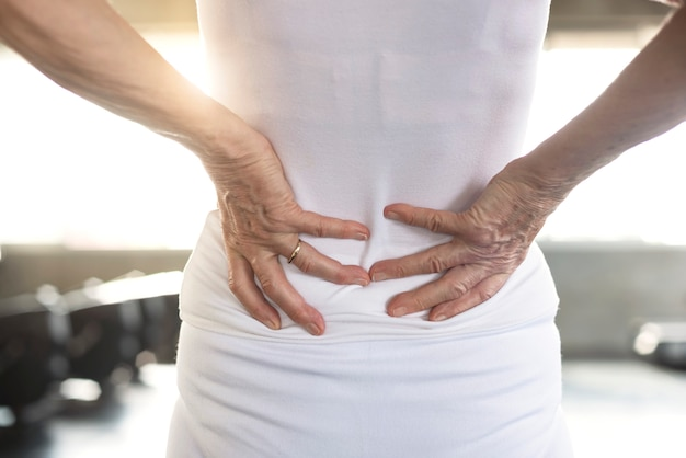 Lesão desportiva, mulher sênior que sofrem de dor nas costas em fitness.