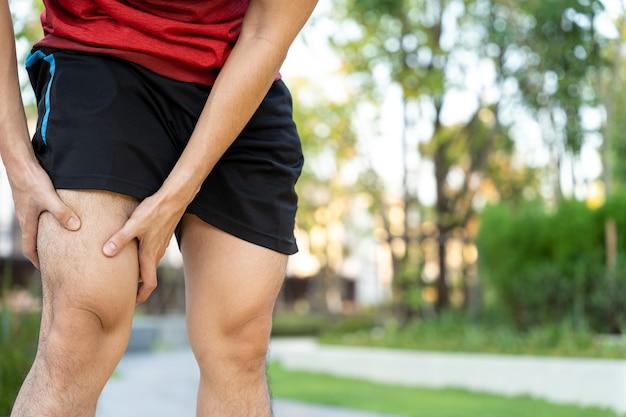 Lesão e dor na perna de atleta corredor masculino. as mãos agarram o joelho dolorido durante a corrida no parque.