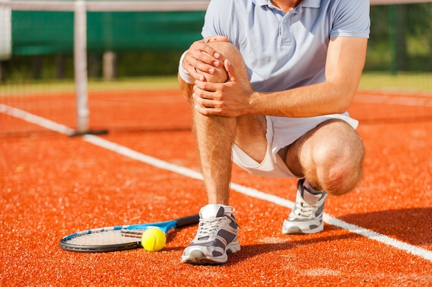 Lesão esportiva. close de um jogador de tênis tocando seu joelho enquanto está sentado na quadra de tênis