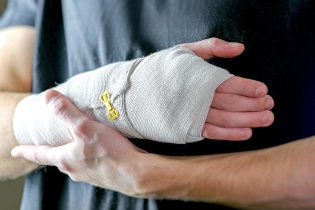 Lesão esportiva da mão cuidados primários a mão é bem fixada com uma bandagem elástica