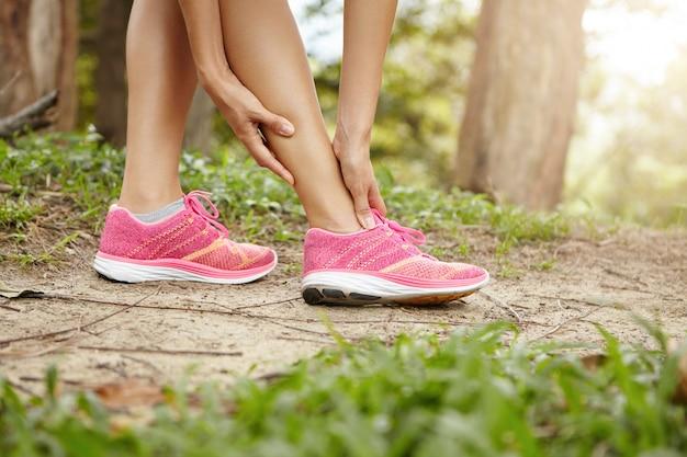 Lesão esportiva em execução. atleta feminina de corrida usando tênis rosa, tocando seu tornozelo torcido ou torcido enquanto corre ou corre ao ar livre.