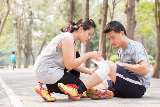 Lesão esportiva. homem com torção no joelho torcido e recebendo ajuda de mulher enfaixada joelho