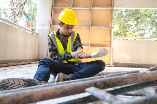 Lesão física no trabalho do trabalhador da construção civil. ferimento sangrando por acidente de trabalho em pilha de aço de andaime caindo e colidindo com o braço.