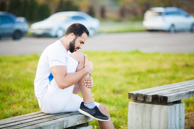 Lesão na perna. atleta masculino, sofrendo de dor na perna durante o exercício ao ar livre