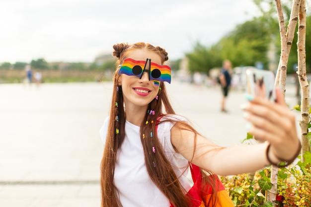 Lésbica na moda em óculos de sol coloridos com arco-íris lgbt no rosto, tendo selfie com smartpthone na praça da cidade