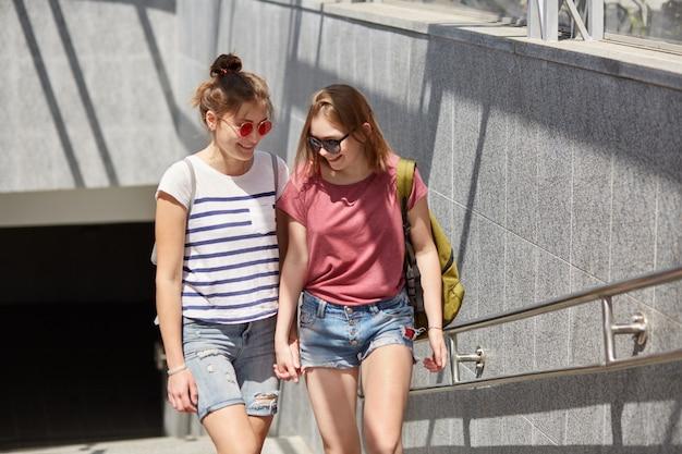 Lésbicas jovens positivas dão as mãos, carregam mochila, camiseta casual e shorts, andam perto do subsolo se divertem juntos