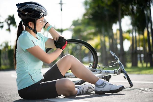 Lesões de bicicleta. o ciclista da mulher caiu caiu da bicicleta da estrada ao andar de bicicleta.