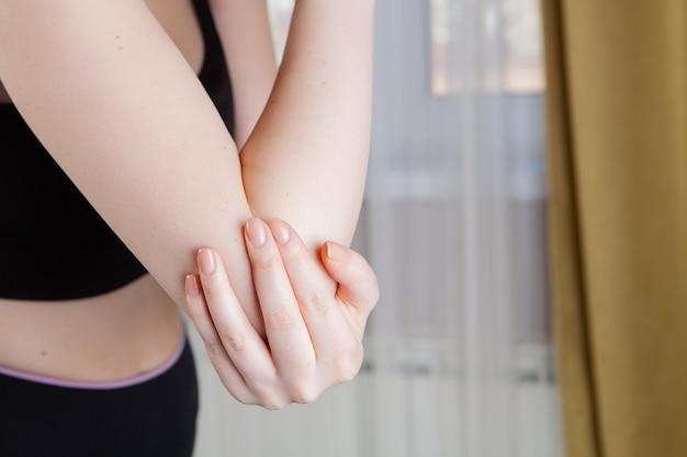 Lesões nas articulações. espasmo no braço da garota.