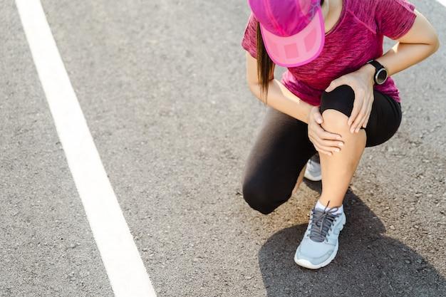 Lesões no joelho. esporte mulher com fortes pernas atléticas, segurando o joelho com as mãos na dor após sofrer lesão muscular durante um treino de corrida na pista de corrida. conceito de saúde e esporte.