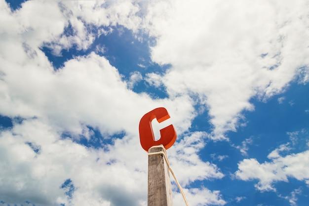 Letra c madeira na frente do céu azul da nuvem