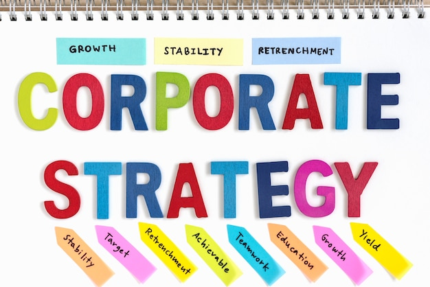 Letra de madeira palavra estratégia corporativa no caderno