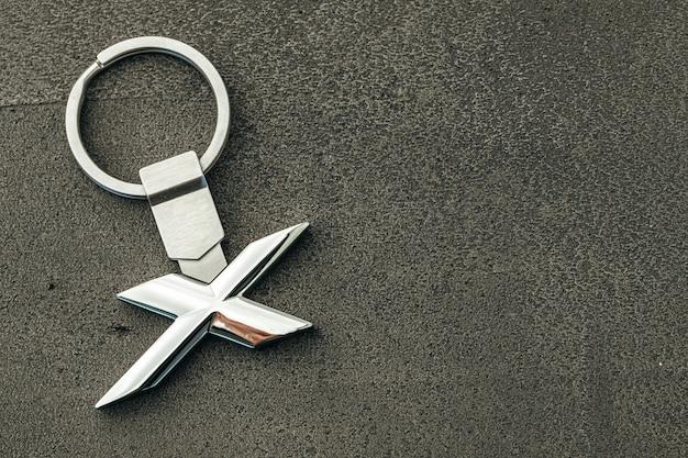 Letra de metal x chave do carro em fundo escuro de concreto close-up