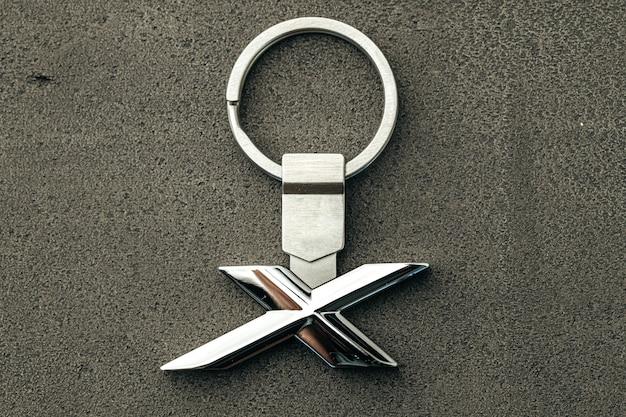 Letra de metal x chave do carro em fundo escuro de concreto