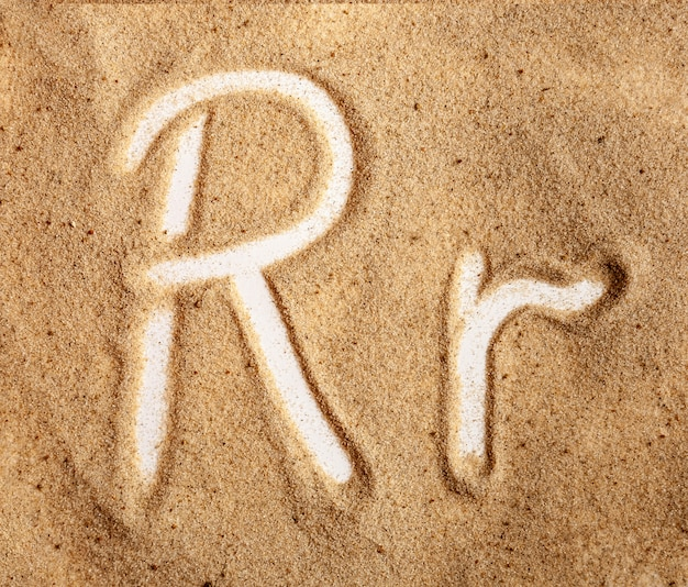 Letra r inglês alfabeto manuscrito na areia