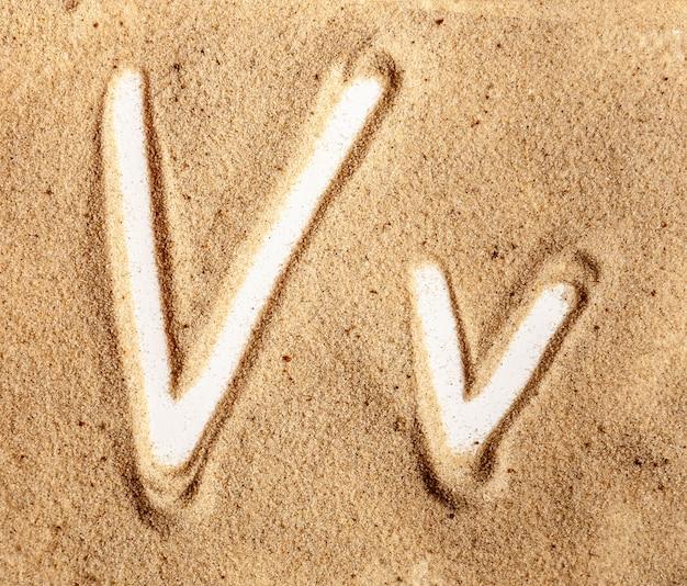Letra v alfabeto manuscrito inglês na areia