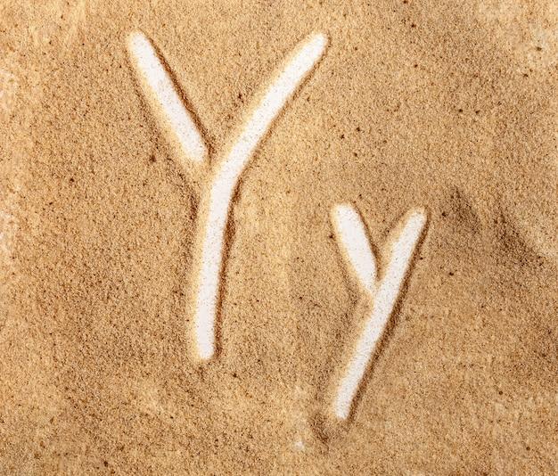 Letra y alfabeto manuscrito inglês na areia