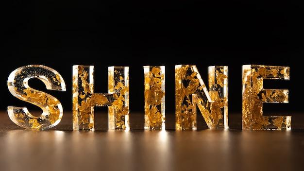 Letras acrílicas com folhas de ouro formando o brilho da palavra na superfície de madeira, fundo preto, foco seletivo.