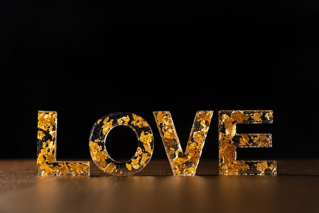 Letras acrílicas com folhas douradas formando a palavra amor em superfície de madeira preta