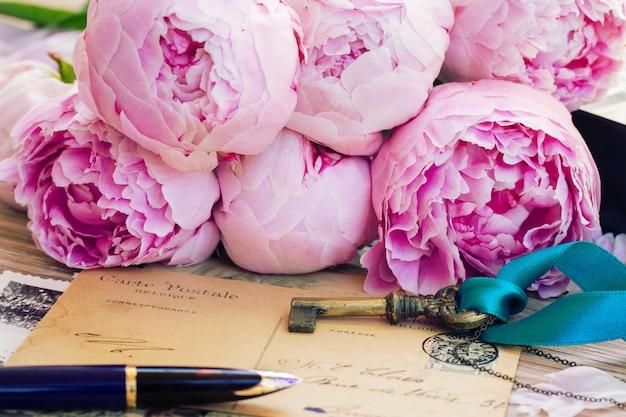 Letras antigas com chave, caneta e flores de peônias frescas