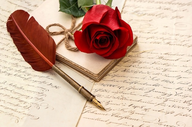 Letras antigas, flor rosa e caneta de pena antiga, fundo vintage romântico