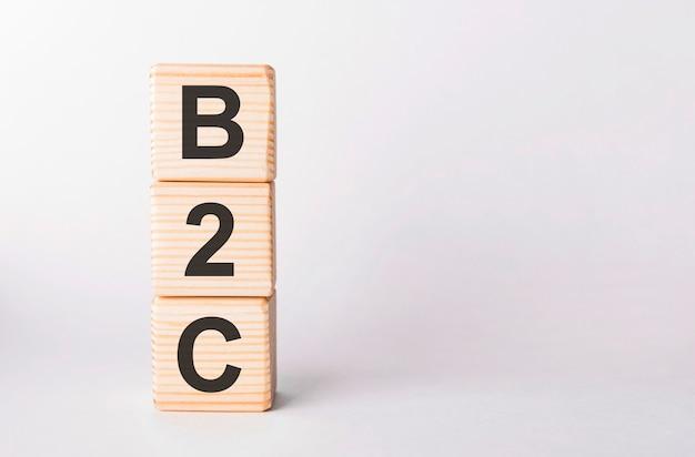Letras b2c de blocos de madeira em forma de pilar em fundo branco, copie o espaço